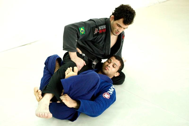 Com o adversário na sua meia-guarda, faça uma pegada na extremidade da calça dele e posicione os pés em X