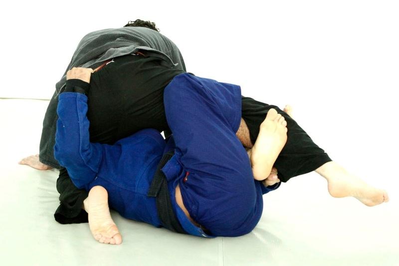 Faça também uma pegada na parte de trás da cintura do oponente, passando o braço por entre as pernas dele