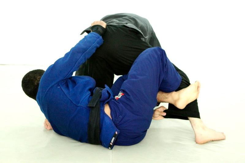 Estique a perna do adversário usando a pegada e os ganchos em X e o empurre para frente com a pegada na cintura, criando espaço para passar a cabeça por entre as pernas do oponente