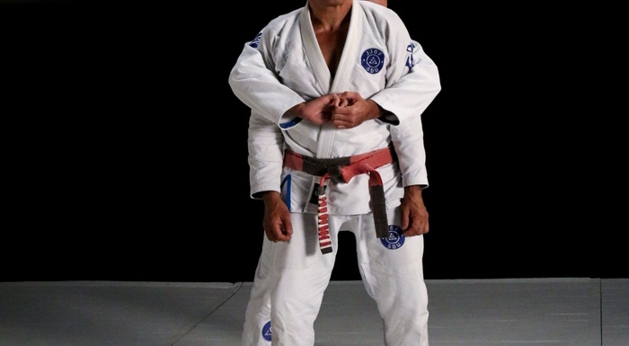 Rickson Gracie teaches: Defense to over-the-arm rear attack