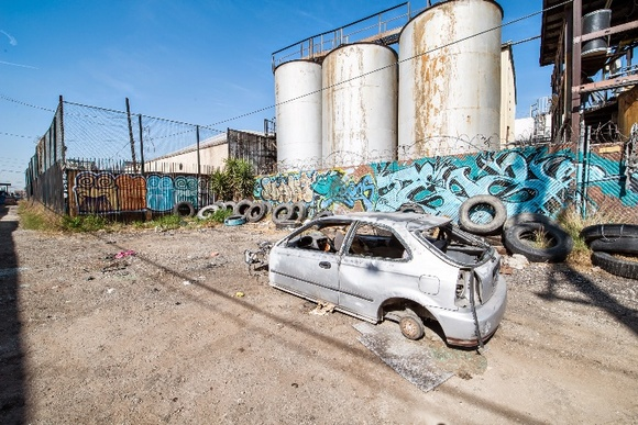Indistrial Alley with Graffiti, Car Skeletons and Metal Barrels. Holding area available inside the studio nearby.