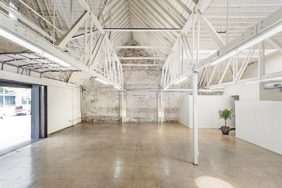 A 6000 sqft warehouse space, with 2 large roll-up doors on the ground level, 20' - 30' ceilings, vaulted ceilings, 6 exposed trusses, whitewashed brick walls, wide expansive spaces, bright with 6 skylights, clean, modern and comfortable. Two large restrooms, separate production, hair and makeup areas, kitchenette with dual sinks, storage space and large refrigerator and can furnish with tables chairs, makeup stations, and other essentials.  Space used by many for its warehouse aesthetic, or as a stage for its expansiveness and use flexibility.