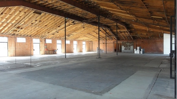 Has approximately 14,500 square feet of production space. It has private, gated parking as well as street parking in the neighborhood. It has exposed brick, vaulted ceilings that are 28 feet, open beams, industrial paneled glass doors, ample power of 1800 amps per building, and a scissor lift with a 28 foot reach onsite for rent.
