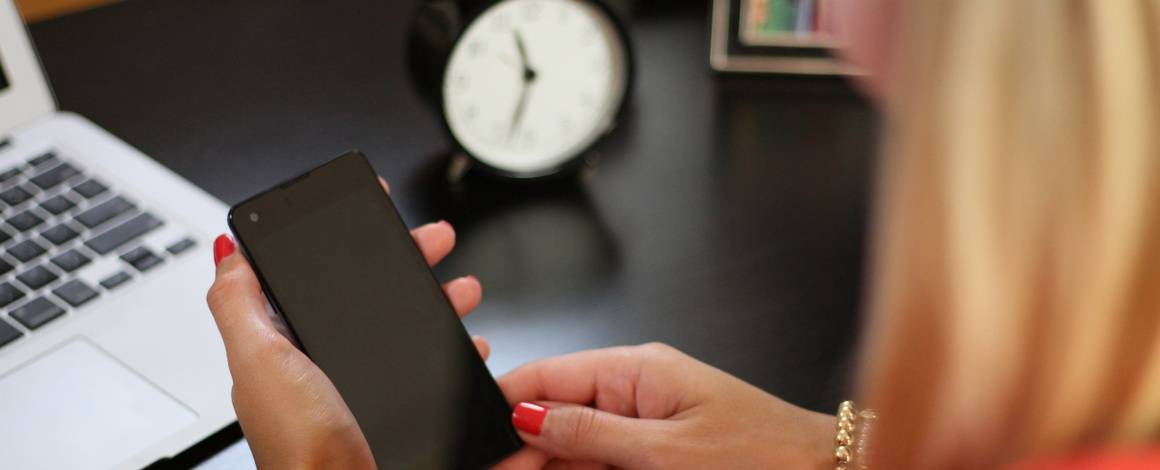 woman looking at phone with clock in background