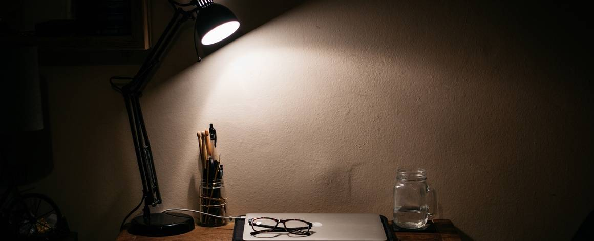 desk at night with laptop  and desk lamp on