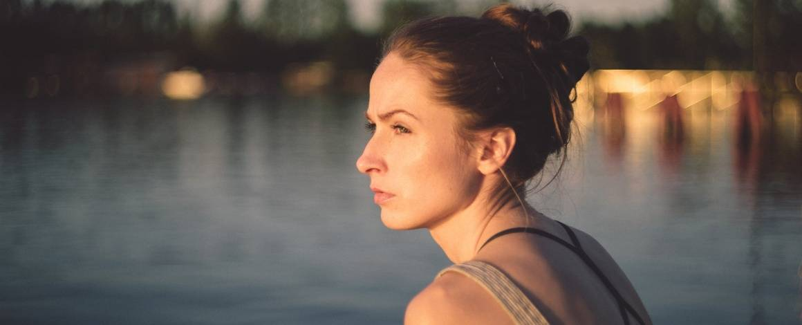woman sitting by water looking to the side