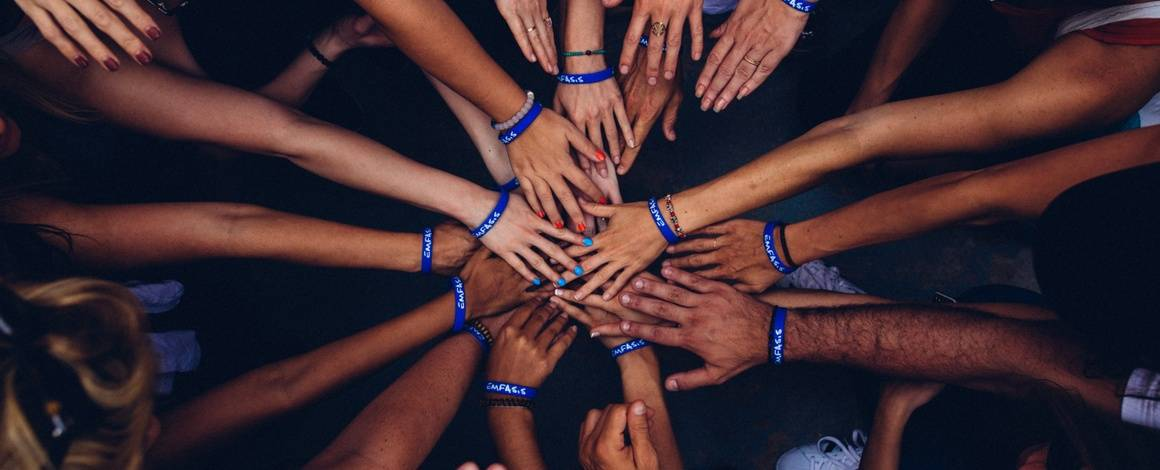 volunteers putting hands in a circle