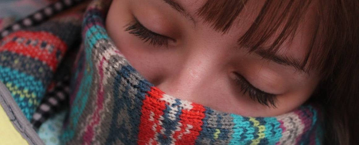 women looking sick with scarf around her nose