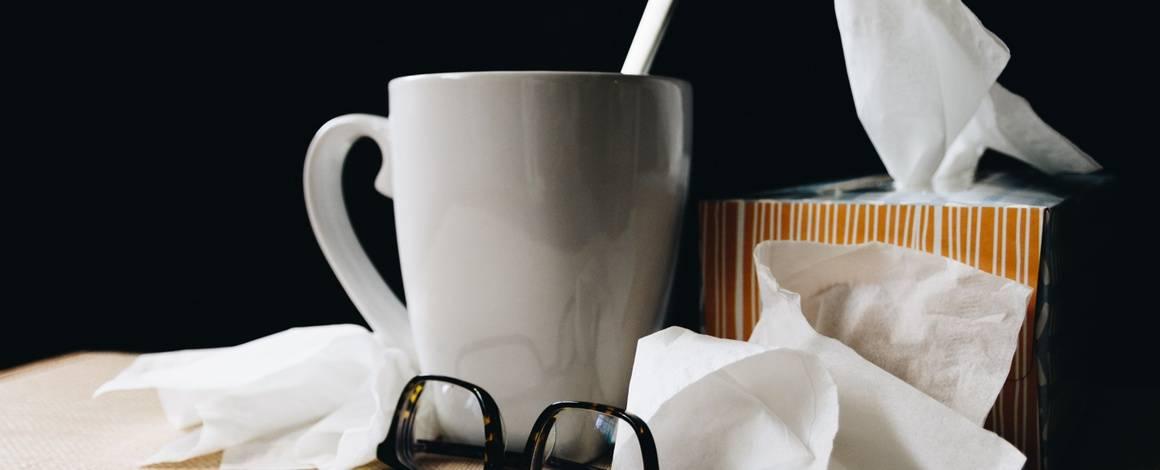 mug, tissues, and glasses on a desk