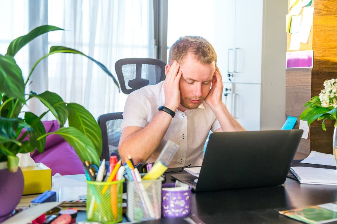 A man sitting at his desk in front of his laptop, rubbing his temples and feeling stressed.