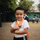 San Jeronimo student with his backpack on smiling at the camera while two students dance in the background