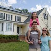 Family of three stands in front of a home with solar. The young girl sits on her dad's shoulders.