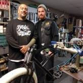 Two men pose with a chopper bicycle they are fixing.
