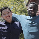 Zak from Kyrgyzstan and Meder from Ghana stretch their arms open and pose with big smiles in North Carolina, USA
