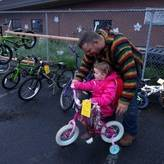 A dad helps his little girl test ride a bike at the Kids Swap