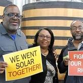 Group of three individuals holding up signs that say we went solar together and fight for our energy rights