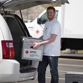 Man loading blood transportation container into Red Cross van