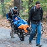 Two Waypoint volunteers pushing and pulling a Waypoint participant on a hiking program.