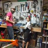 Bike shop manager Josh with a boy helping to fix bikes