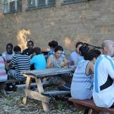 People of many ages and races sitting at outdoor picnic tables enjoying an evening meal