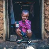 Young boy in Tanzania enjoys a glass of clean, safe water.