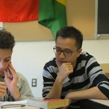 Middle school student in a hoodie and adult tutor with glasses look at a problem together.