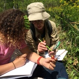 Adult and student outdoors recording nature in notebooks